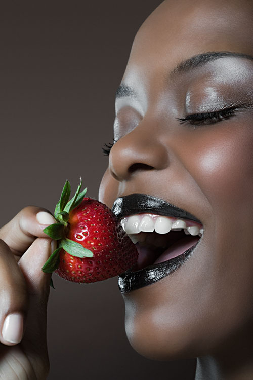 Beautiful woman biting seductively into strawberry