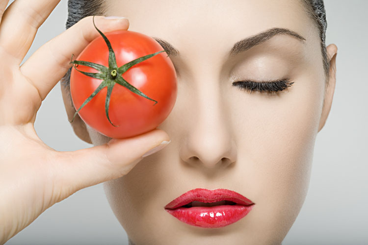 Woman holding tomato to her eye